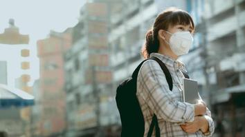 Female student walking through a city wearing a face mask